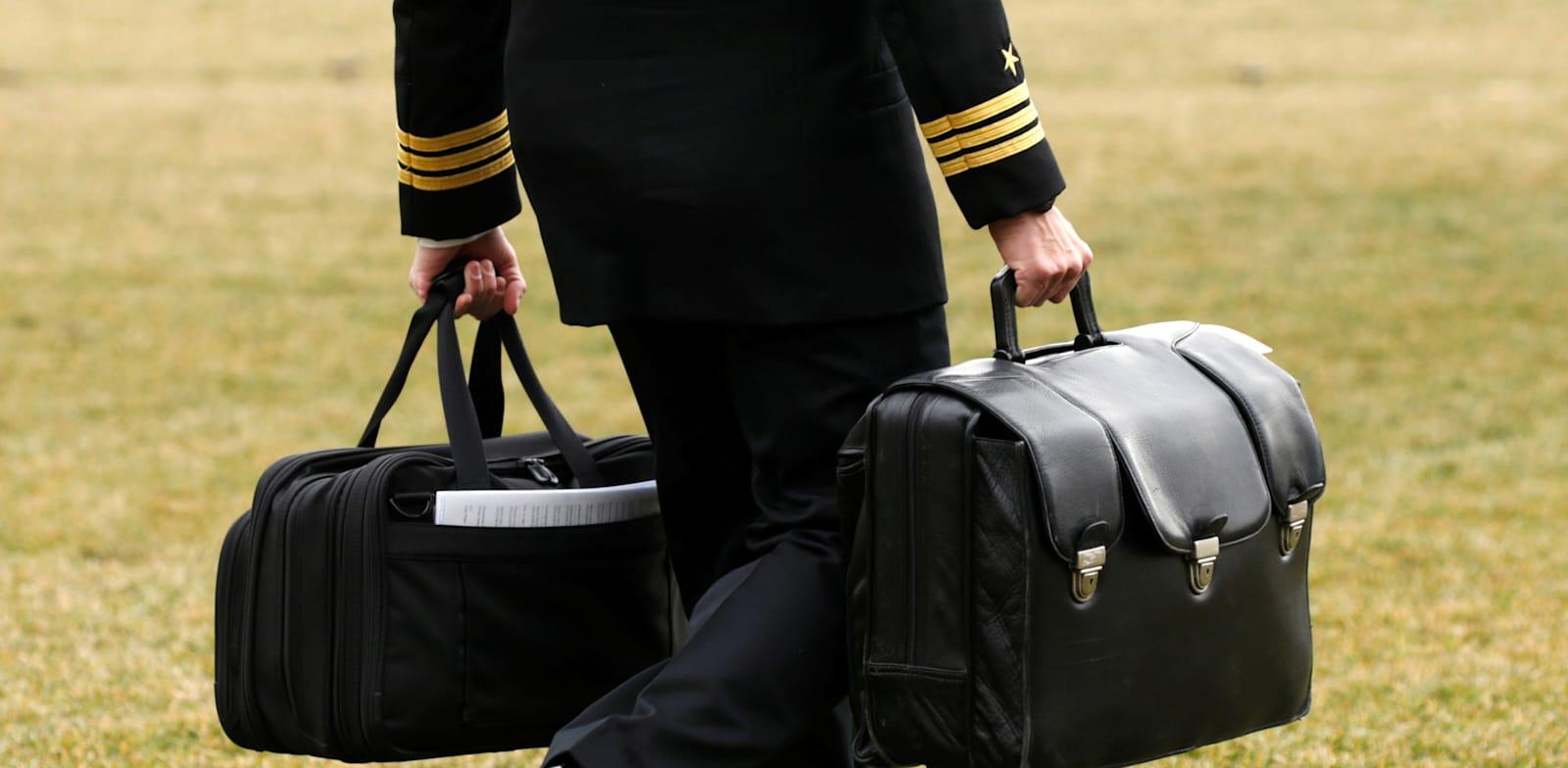 """חייל מארינס נושא את """"הפוטבול"""" עם הצפנים לפצצות הגרעין / צילום: Reuters, Kevin Lamarque"""