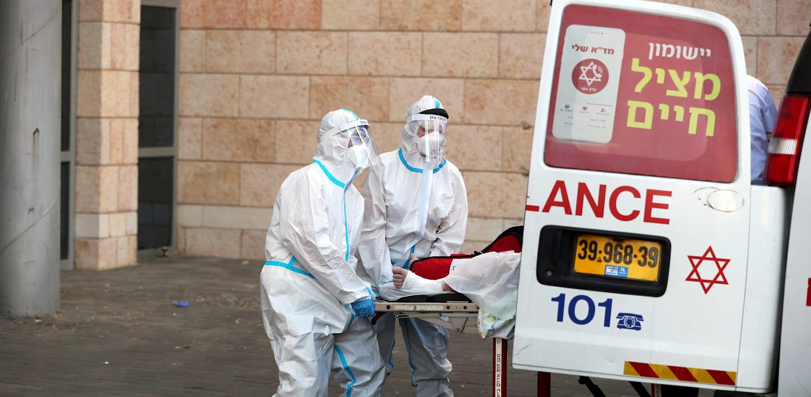 """פרמדיקים מכניסים חולה קורונה לביה""""ח, בירושלים / צילום: Reuters, Ammar Awad"""