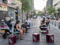 ארגזי בירה משמשים ככיסאות לישיבה ליד / צילום: כדיה לוי