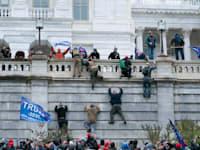 מפגינים מטפסים על קירות הקפיטול בניסיון לפרוץ לבניין / צילום: Associated Press, Jose Luis Magana