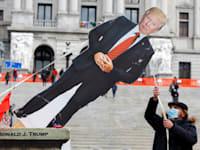 מפגין מוריד בובת טראמפ שהוצבה מול בית הנבחרים של פנסליבניה, זמן קצר לפני הפגנה של תומכי הנשיא נגד תוצאות הבחירות / צילום: Reuters, Rachel Wisniewski