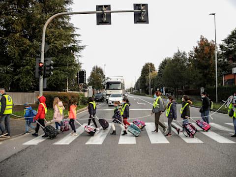 תלמידים איטלקים בבלוסקו צועדים לבית הספר בקבוצות שבהן הריחוק החברתי נשמר באמצעות חבלים / צילום: Associated Press, Luca Bruno