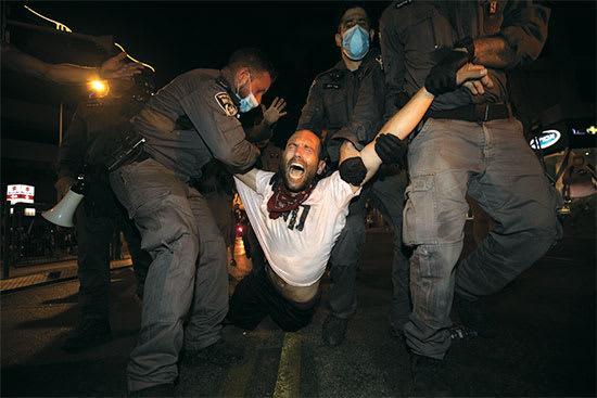 """מפגין נעצר בתל אביב.  """"לא תמצא באולפנים  נציגים של המוחים"""" / צילום: Associated Press, Sebastian Scheiner"""