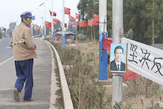 כפרי מתבונן בתמונתו של נשיא סין שי ג'ינפינג / צילום: Reuters, Wong Campion