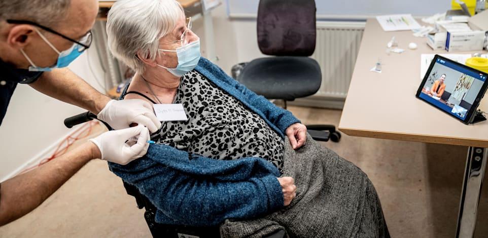 """קשישה דנית מקבלת את אחד החיסונים הראשנים במדינה, כשרה""""מ פרדריקסן צופה בה בטאבלט / צילום: Reuters, RITZAU SCANPIX"""