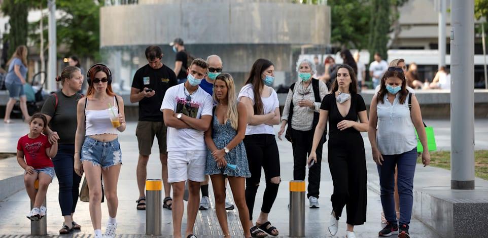 אנשים עומדים במעבר חצייה בתל אביב ביוני האחרון / צילום: Reuters, Amir Cohen