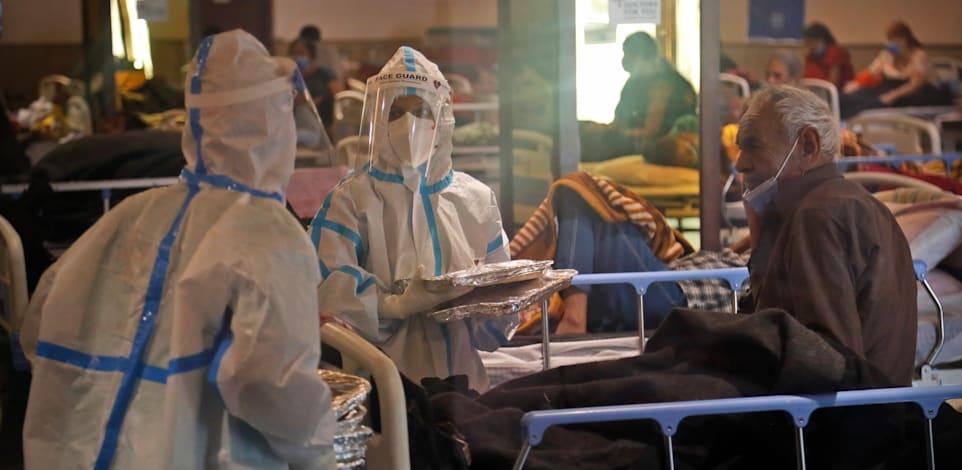 צוות רפואי עובר בין החולים במרכז בידוד בניו דלהי. הצוותים הרפואיים קורסים תחת עומס החולים ברחבי המדינה / צילום: Associated Press, Manish Swarup