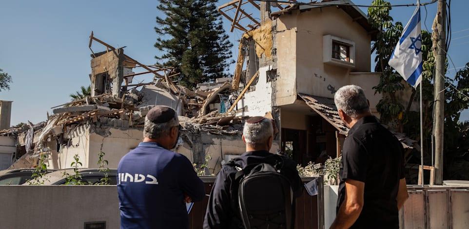 אנשים מבטים בבית ביהוד שספג פגיעה ישירה מרקטה ששוגרה מעזה / צילום: Associated Press, Heidi Levine