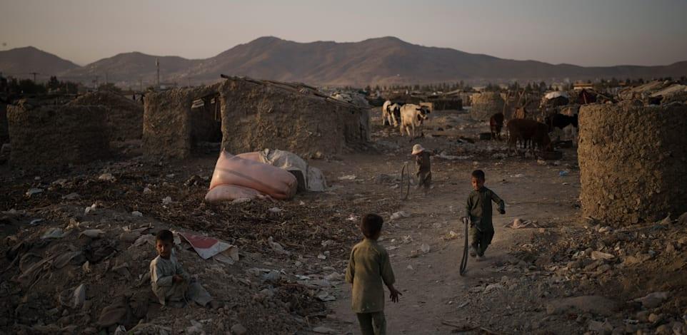 ילדים אפגנים משחקים בשכונה ענייה בפאתי קאבול שבה מתגוררים מאות אנשים עקורים / צילום: Associated Press, Felipe Dana