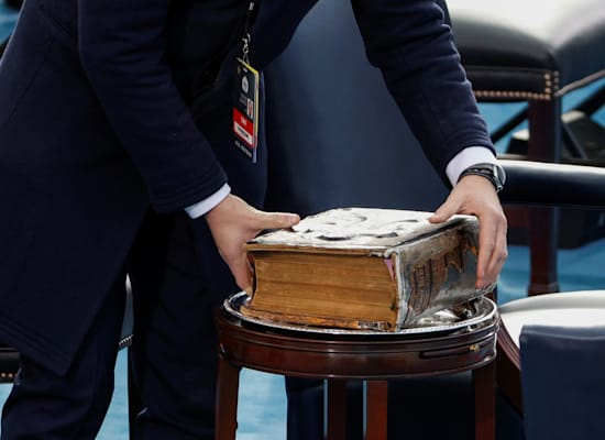 """עובד מניח את התנ""""ך שעליו יושבע ג'ו ביידן לקראת ההשבעה / צילום: Reuters, Brendan McDermid"""