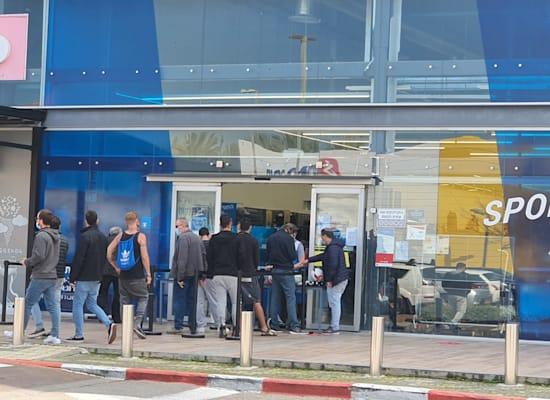אנשים עומדים בתור לדקלטון במרכז ביג בקריות. רשתות הציבו שולחן בכניסה לחנות ומכרו דרכו / צילום: פאול אורלייב