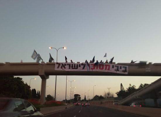 מפגינים נגד ראש הממשלה בנימין נתניהו והשחיתות השלטונית בגשר כפר שמריהו / צילום: הדגלים השחורים