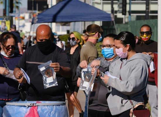 אזרחים אמריקאים מפקידים ערכות בדיקה לקורונה בלוס אנג'לס, בחודש שעבר / צילום: Associated Press, Richard Vogel
