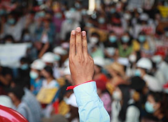 מפגין מרים את ידו לסמל המאבק במשטר הצבאי / צילום: Associated Press