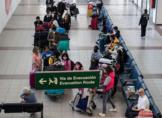 נוסעים שהגיעו לצ'ילה מחכים להסעה שתיקח אותם לבידוד במלונית למשך חמישה ימים / צילום: Associated Press, Esteban Felix