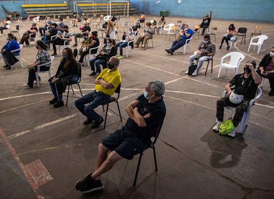 אנשים בצ'ילה יושבים להשגחה אחרי שקיבלו חיסון נגד קורונה / צילום: Associated Press, Esteban Felix