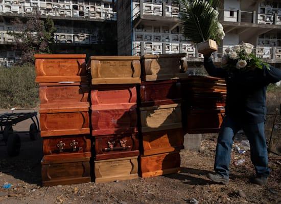 עובד בבית קברות בצ'ילה מסדר ארונות קבורה ריקים לאחר שהמתים נשרפו / צילום: Associated Press, Esteban Felix