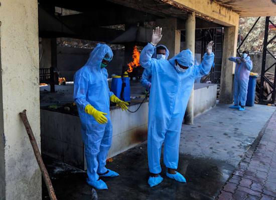 צוות רפואי מחטא את עצמו לאחר שריפת גורמות קורונה / צילום: Associated Press, Rafiq Maqbool