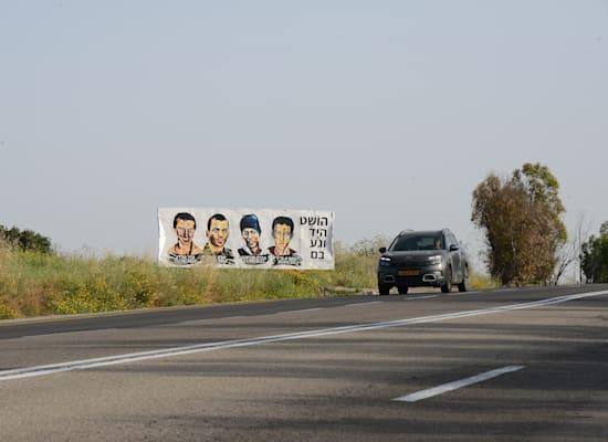 בדרך לקיבוץ נחל עוז, שלט גדול עם ארבע דמויות מאוירות: אברה מנגיסטו, הישאם א-סייד, הדר גולדין ואורון שאול / צילום: איל יצהר