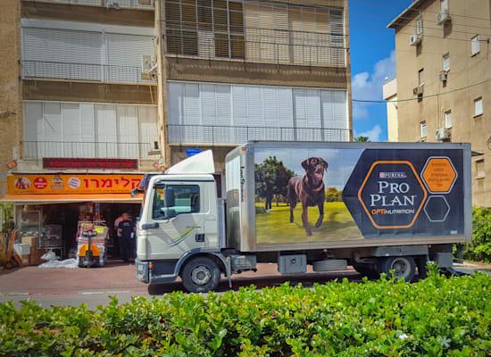 """משאית פורקת סחורה בחזית בניין בראשל""""צ / צילום: Shutterstock"""