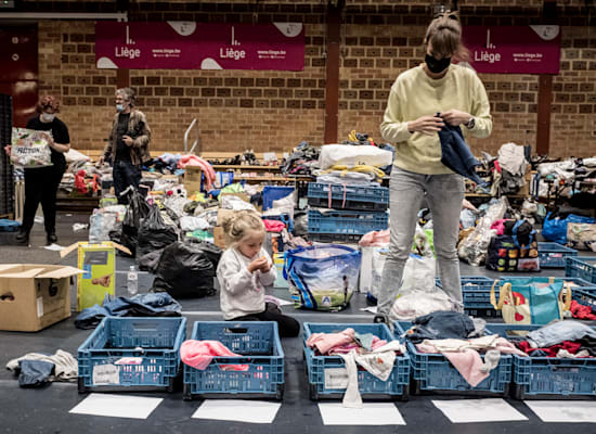 אישה ממיינת בגדים בבית מחסה לנפגעי השיטפונות באנגלאור, בלגיה / צילום: Associated Press, Valentin Bianchi