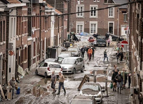 תושבי עירייה במחוז לייז' בבלגיה הולכים ברחוב הרוס לאחר שהמים ירדו / צילום: Associated Press, Valentin Bianchi