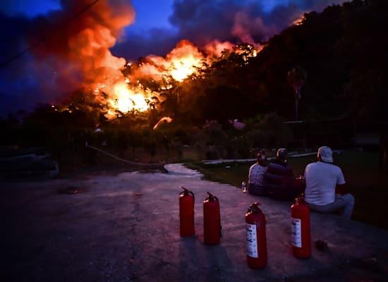 אנשים, רגע לפני הפינוי מהמקום, צופים בשריפות באזור היסרונו הטורקי / צילום: Associated Press