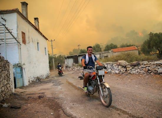 אדם בורח מהאש בעירייה קוקרטמה, שסמוכה לבודרום בטורקיה / צילום: Associated Press, Emre Tazegul