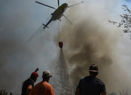 מוסק שופך מים על שריפה שמשתוללת בכפר ליד העיר הטורקית מנבגט / צילום: Associated Press