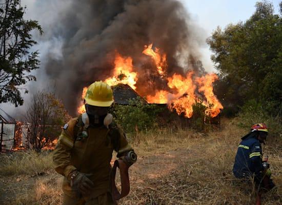 כבאים מנסים להשתלט על שריפה בכפר ליד העיר היוונית פטרס / צילום: Associated Press, Andreas Alexopoulos