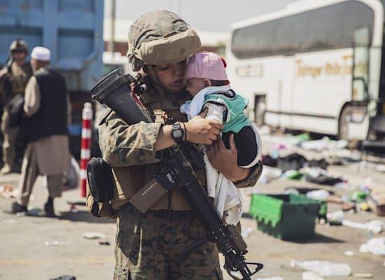 חיילת מארינס אמריקאית עם תינוק אפגני בשדה התעופה בקאבול, בשבת / צילום: Associated Press, Staff Sgt. Victor Mancilla