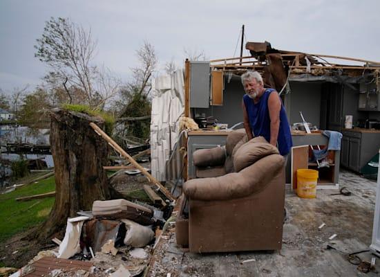 אדם עומד עם מה שנשאר מהסלון שלו אחרי שהוריקן איידה פגע בעיר לוקפורט, בלואיזיאנה / צילום: Associated Press, John Locher