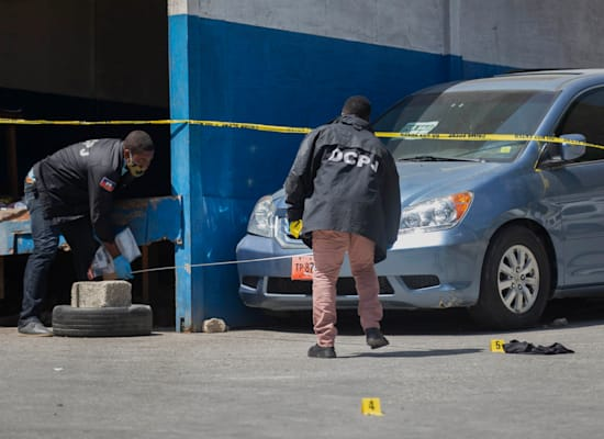 משטרת האיטי אוספת ראיות מזירת הרצח. חילופי אש פרצו בשכונה / צילום: Associated Press, Joseph Odelyn