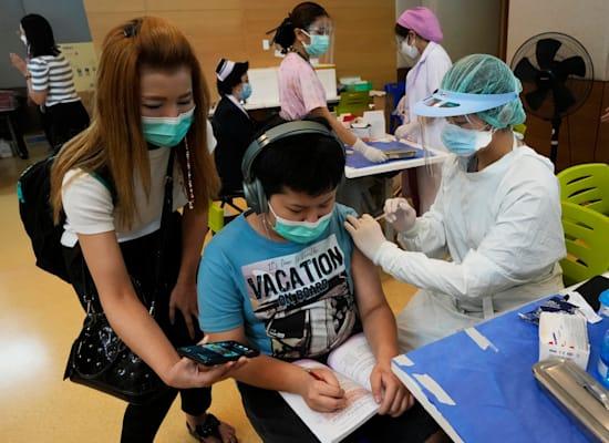 ילד מקבל חיסון של פייזר תוך כדי שהוא ניגש למבחן מקוון ואימו מחזיקה את הטלפון הנייד עם הבחינה, בבית חולים בנגקוק בתאילנד / צילום: Associated Press, Sakchai Lalit