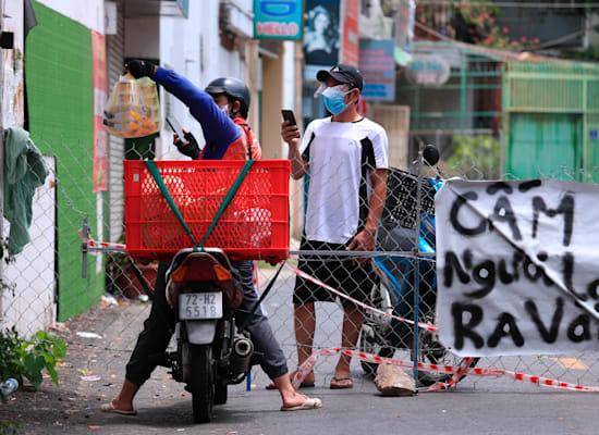 שליח מביא אוכל לאדם ברחוב שנמצא בבידוד כחלק מהגבלות הקורונה. וונג טאו, וייטנאם באמצע ספטמבר / צילום: Associated Press, Hau Dinh