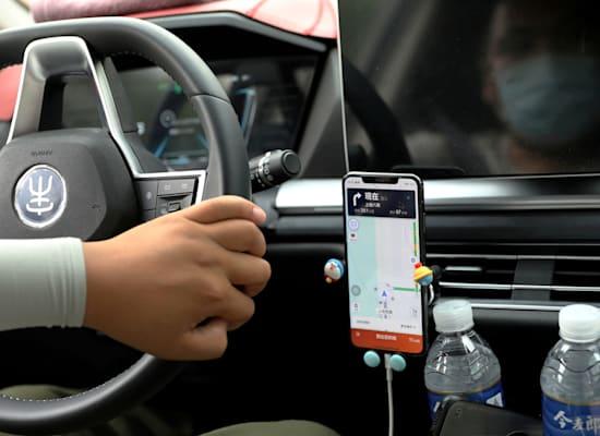 נהג בבייג'ינג' משתמש באפליקציית הנסיעות של דידי / צילום: Reuters, Tingshu Wang