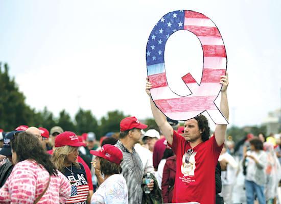 מפגין אוחז בשלט של QAnon. בפייסבוק לא מתמודדים היטב עם הפצת מידע כוזב וקונספירציות / צילום: Associated Press, Matt Rourke