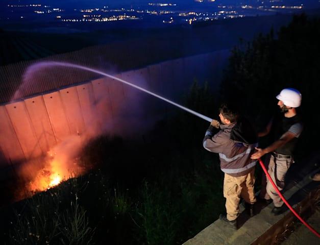 אנשי חיזבאללה מכבים אש שפרצה לאחר המהומות בגבול לבנון / צילום: Associated Press, Hussein Malla