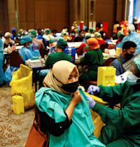 """חיסון עובדים במפעל באינדונזיה. ביקורת נגד הממשלה כי החיוב להתחסן """"מנוגד לזכויות האדם"""" / צילום: Reuters, Ajeng Dinar Ulfiana"""