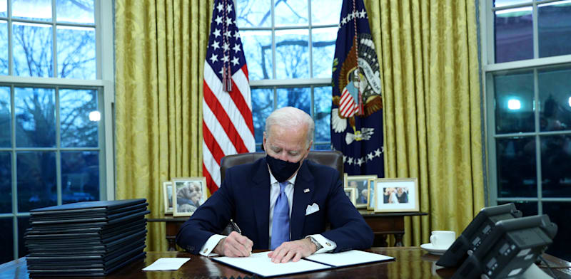 Joe Biden signs executive orders on becoming US president   credit: Tom Brenner, Reuters