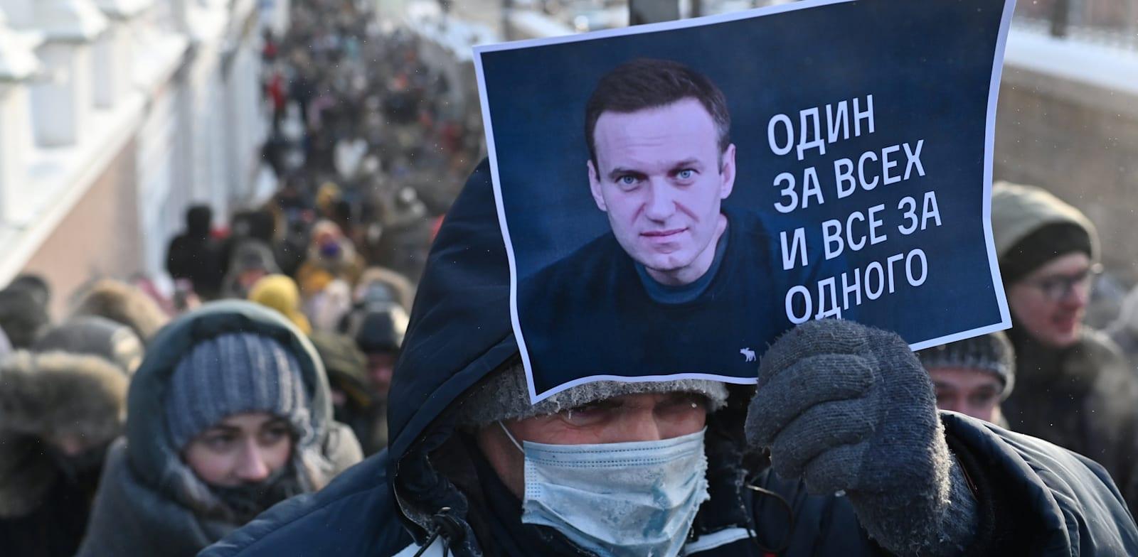 """מפגין אוחז בשלט עם תמונתו של אלכסיי נבלני והכיתוב """"אחד בשביל כולם, כולם בשביל אחד"""" / צילום: Reuters, Alexey Malgavko"""