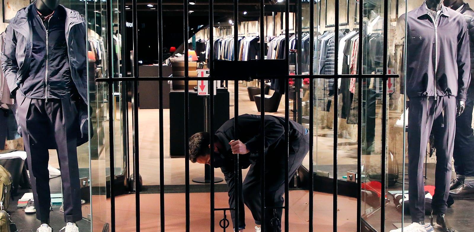 אדם סוגר את חנותו כמה דקות לפני העוצר, בסן ז'אן דה לוז בדרום מערב צרפת, לפני כשבועיים / צילום: Associated Press, Bob Edme