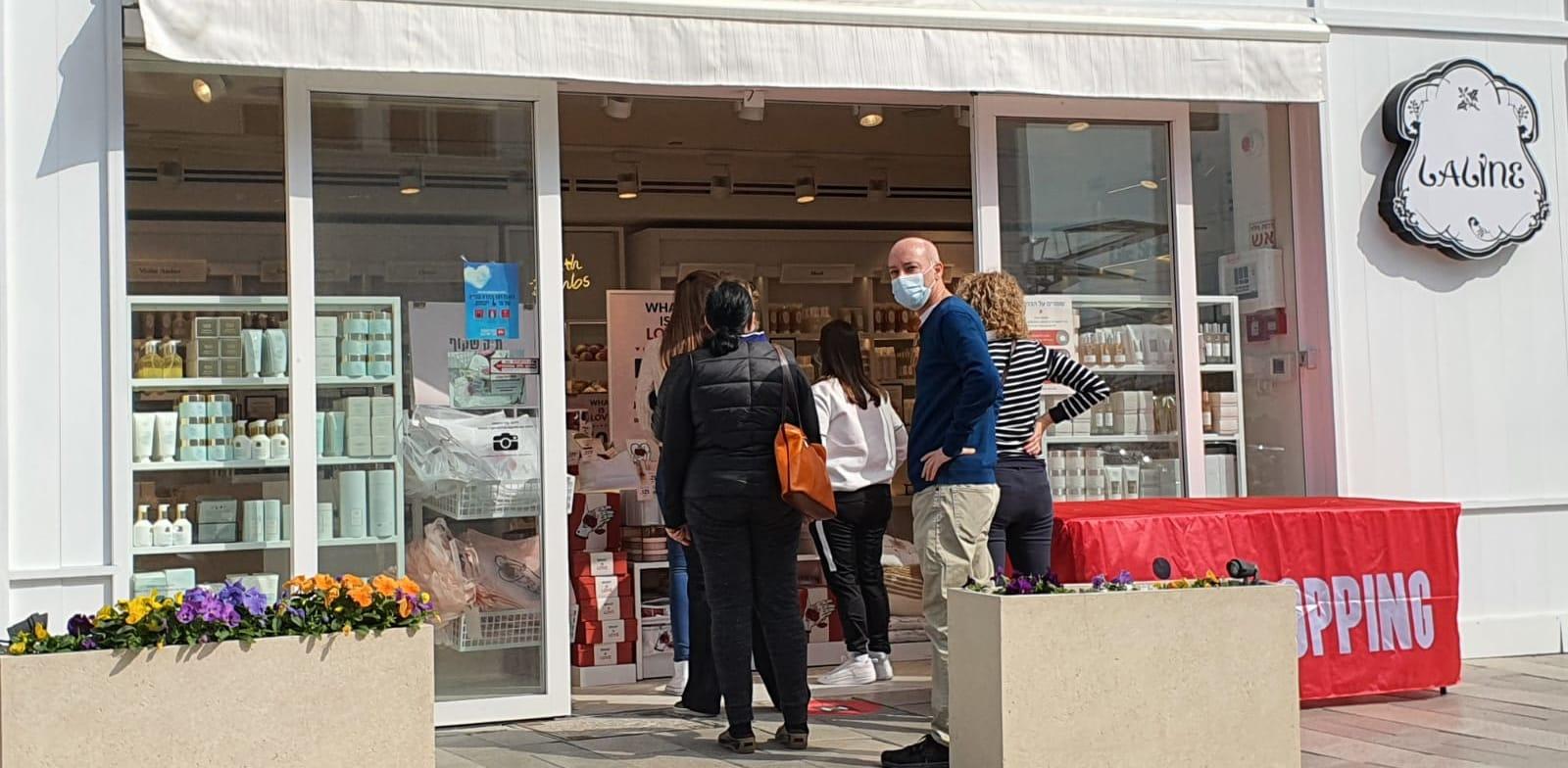 אנשים עומדים בתור לחנות ללין במרכז ביג בקריות. רשתות רבות נפתחו בניגוד להנחיות הסגר / צילום: פאול אורלייב