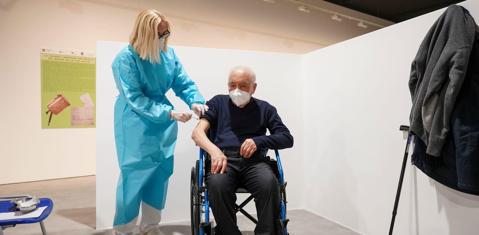 קשיש מקבל מנת חיסון של מודרנה במרכז חיסונים ברומא, איטליה / צילום: Associated Press, Andrew Medichini