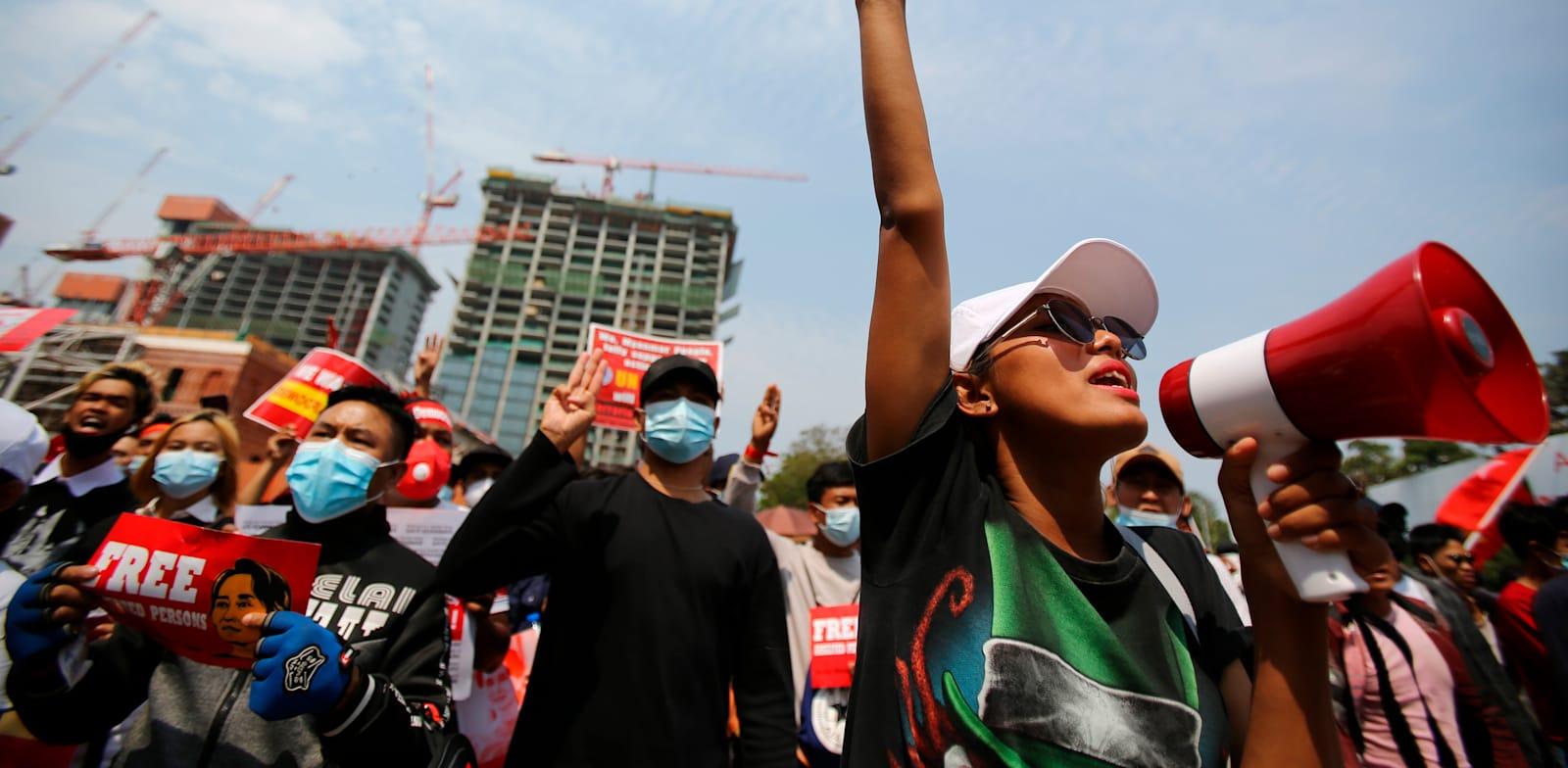 """מפגינה מצביעה בשלוש אצבעות, סמל המאבק, זאת לאחר שמפגינה נורתה בראשה ע""""י המשטר הצבאי במסגרת ההפגנות / צילום: Associated Press"""