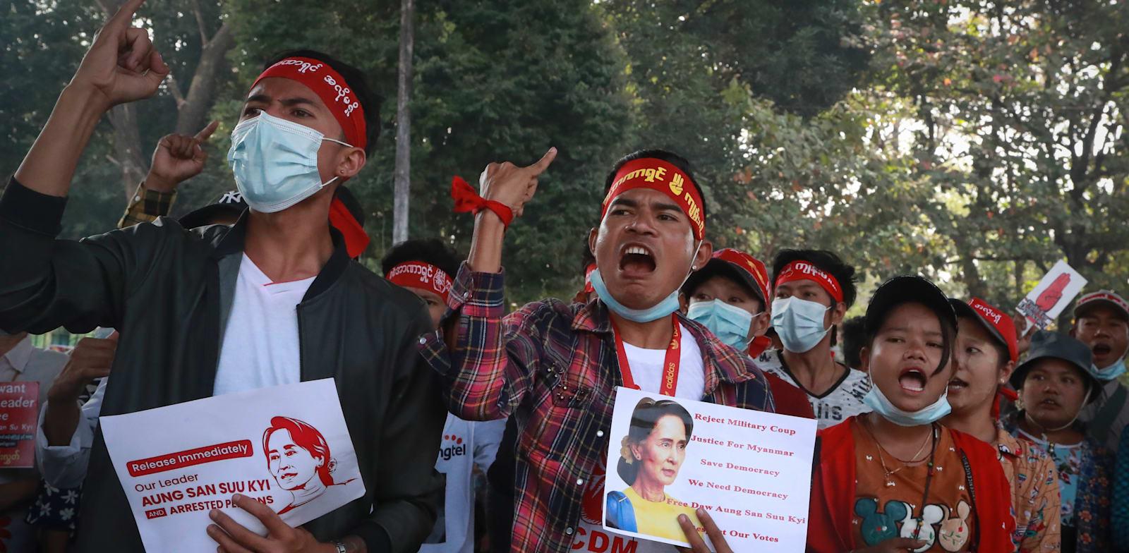 צעירים מפגינים אוחזים תמונה של ראש ממשלתם העצורה / צילום: Associated Press