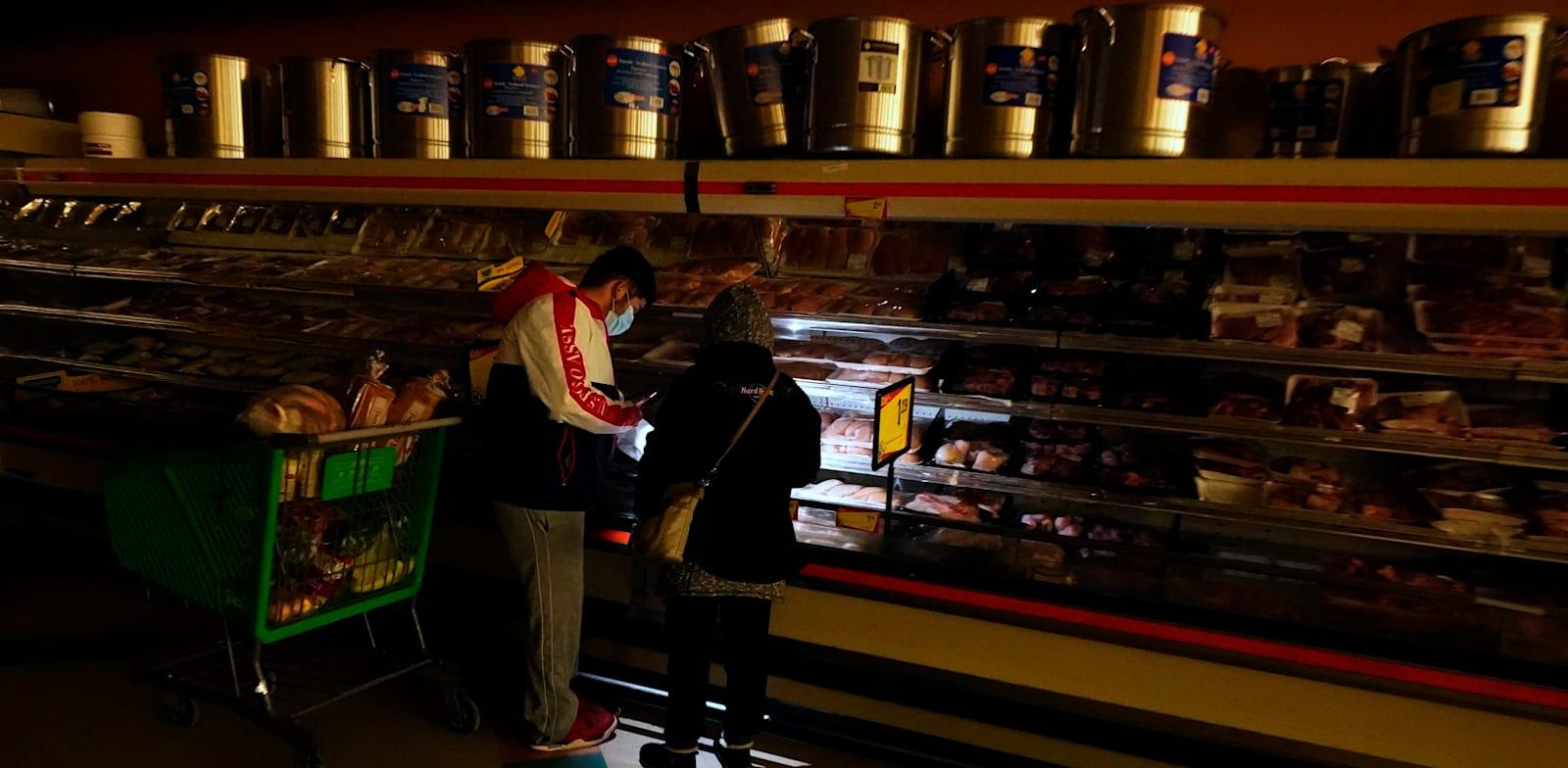 טקסנים משתמשים בפנס של הטלפון הסלולרי כדי לראות את המצרכים בחנות בדאלאס בזמן הפסקת החשמל / צילום: Associated Press, LM Otero