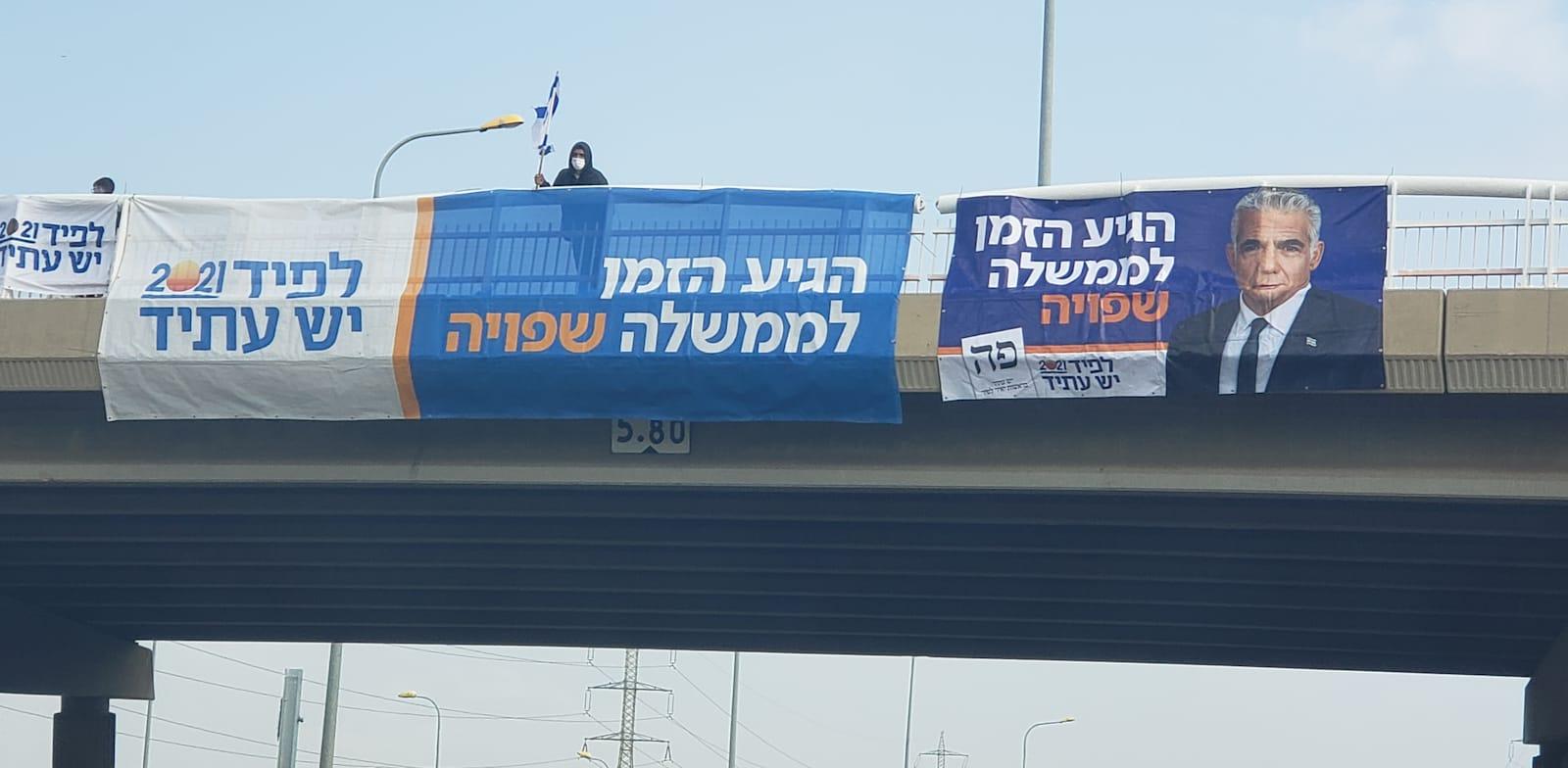 שלטי בחירות של מפלגת יש עתיד על גבי גשר / צילום: דלית איזיק לויתן