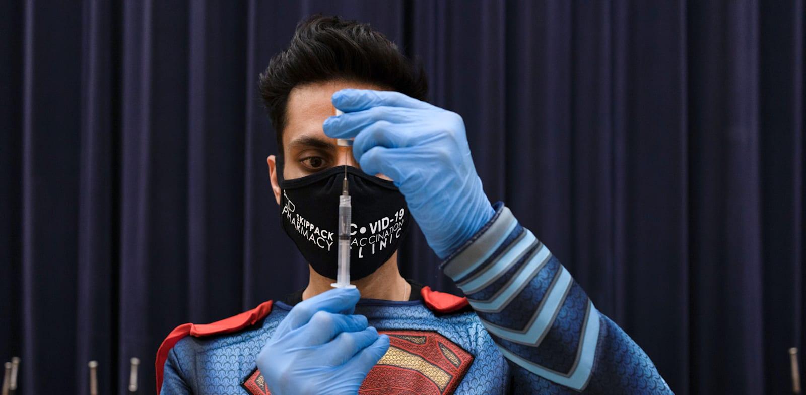 """רופא מחסן בחיסון של פייזר נגד קורונה בפנסילבניה, ארה""""ב / צילום: Reuters, Hannah Beier"""