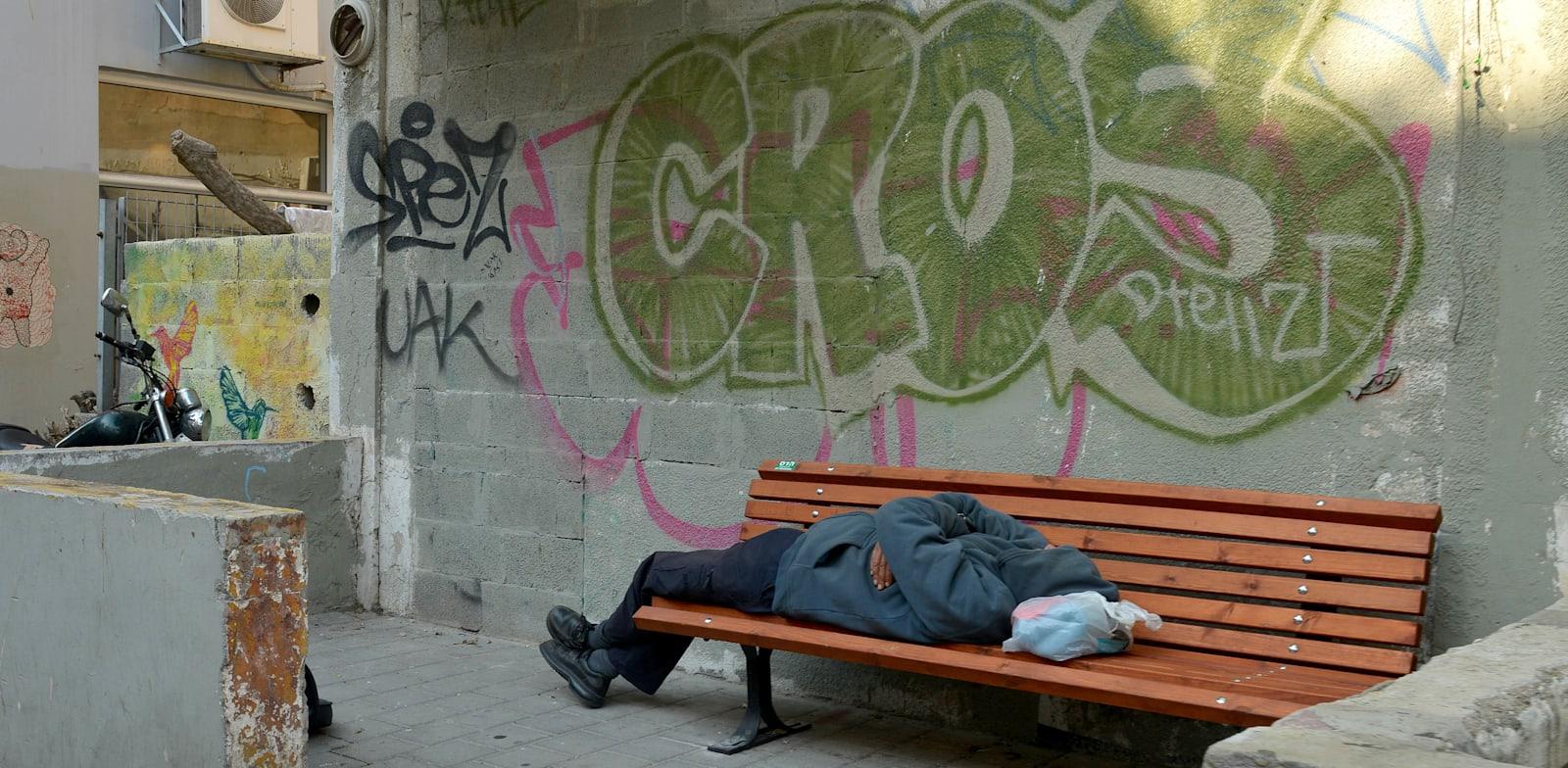 הומלס שוכב על ספסל ברחוב / צילום: תמר מצפי